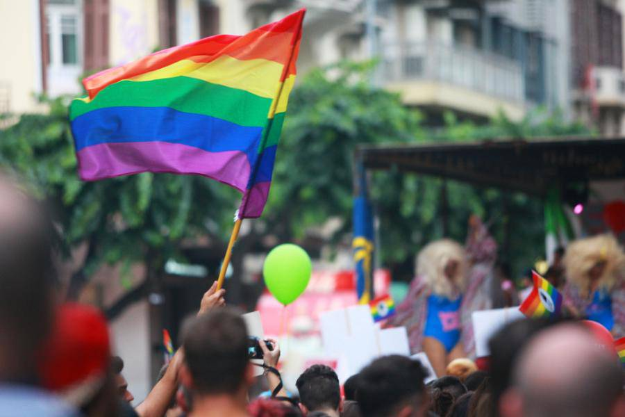 tęczowa flaga trzymana przez uczestnika parady