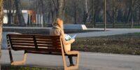 Kobieta czytająca gazetę na ławce w Parku Ludowym