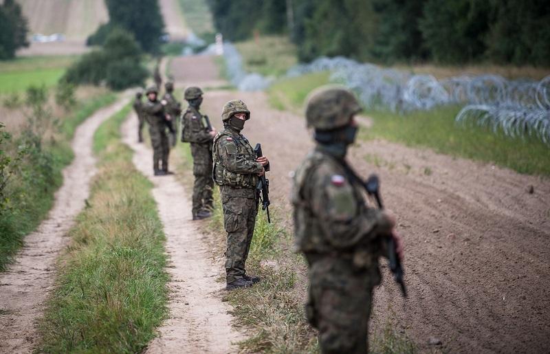 Żołnierze pilnujący płotu na granicy polsko-białoruskiej