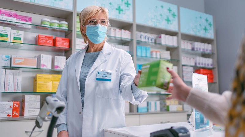 aptekarka podająca klientowi lek