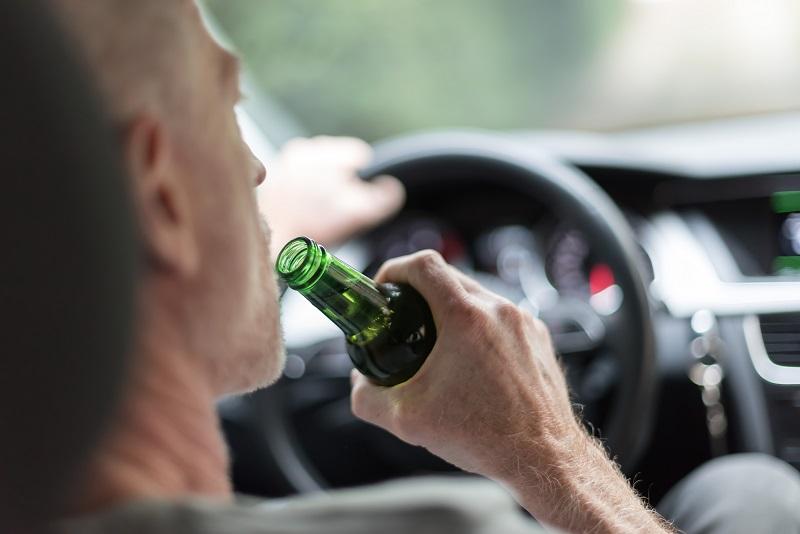 Mężczyzna pijący piwo podczas jazdy