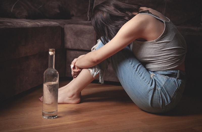 Kobieta z butelką wódki w domu