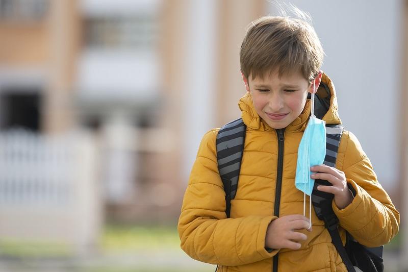uczeń ściągający maseczkę po wyjściu ze szkoły