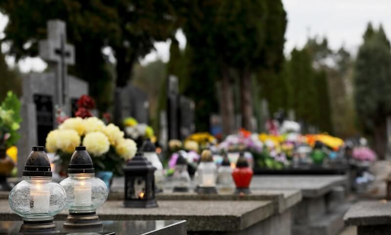 bukiet kwiatów w wazonie na cmentarzu, znicze na grobie