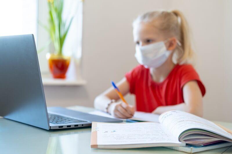 Uczennica odrabiająca lekcje w maseczce przed komputerem